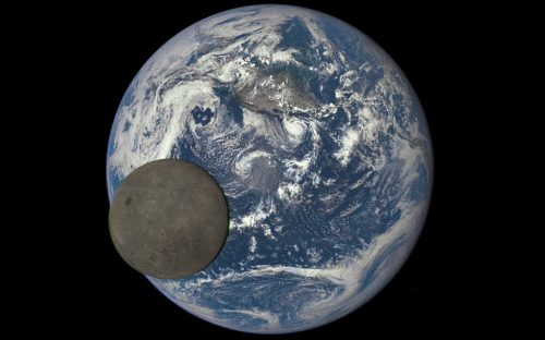Our blue planet with the moon crossing.